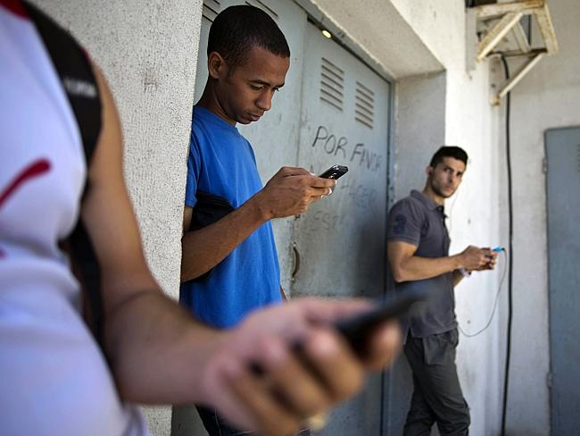 Limited access ... students gather behind a business looking for an internet signal for their smartphones in Havana.
