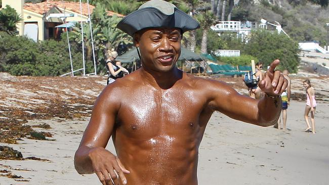 Cuba frolics shirtless on the sand and tugs down his shorts during a beach outing in Malibu.