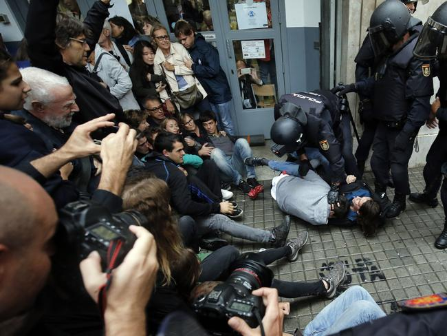 Spanish police officers immobilise some people outside a polling station in Barcelona. Picture: AFP