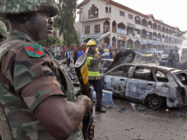 Horror ... a Nigerian soldier stands guard after an explosion rocked a shopping mall in Nigeria's capital, Abuja. Picture: AP Photo/Olamikan Gbemiga