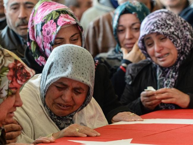 Grief-stricken ... relatives of car bombing victim Murat Gul mourn over a coffin during the funeral ceremony in Ankara, Turkey. Picture: Gokhan Tan/Getty Images