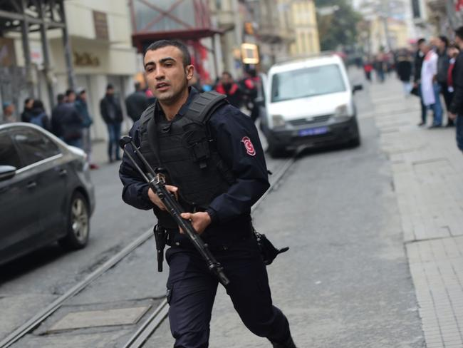 A Turkish policeman clears the streets after the explosion. Picture: AFP/Bulent Kilic