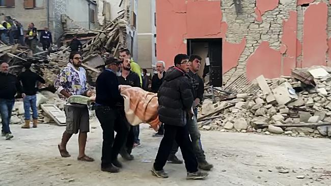 Rescuers recover a victim from a crumbled building in Amatrice, central Italy. Picture: AP.