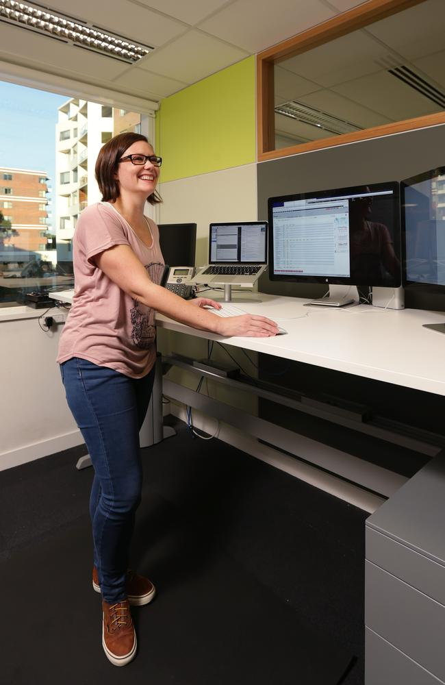 Standing up stops you ageing ... Carlee Potter at work with adjustable stand up/sit down desks.
