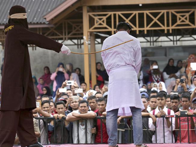 A sharia law official whips a man convicted of adultery with a rattan cane in Banda Aceh last month. Picture: Heri Juanda