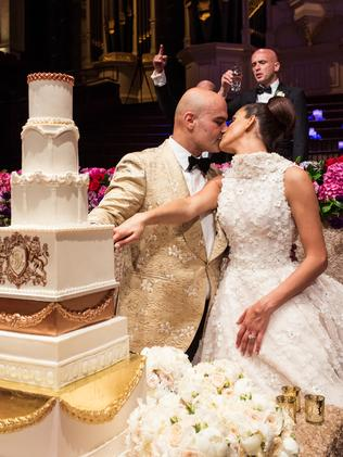 The couple share a kiss as they cut their seven-tiered wedding cake.