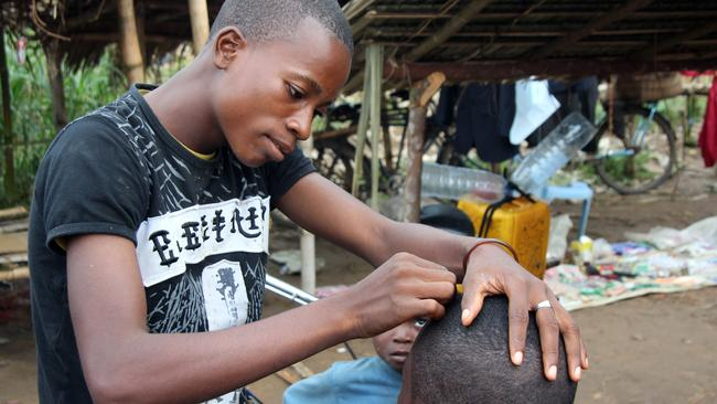 High risk ... a Congolese hairdresser cuts hair in Lokolia in the Democratic Republic of Congo despite the authorities' order to avoid physical contact to stop the spread of the Ebola virus. Picture: AFP