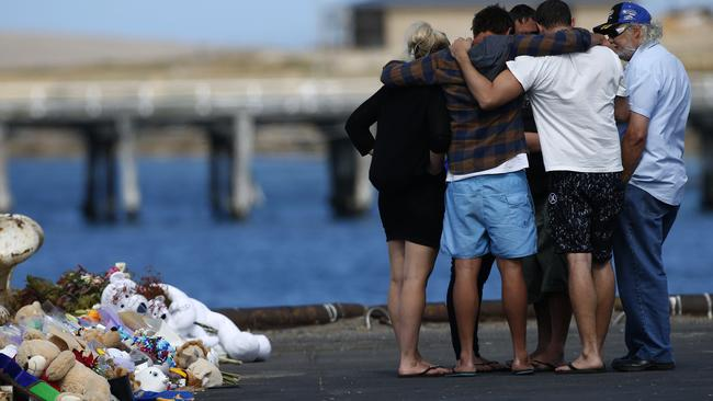 Hunter and Koda's uncles, and Damien's brothers, are comforted by family at the scene. Picture: Dean Martin