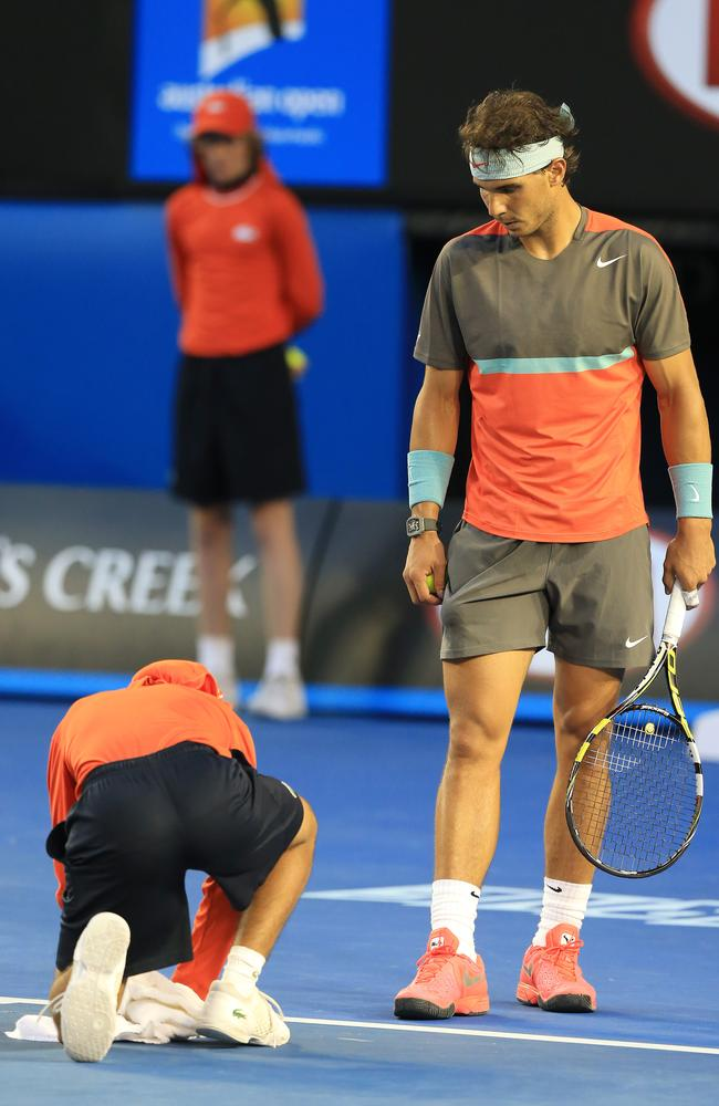 Rafael Nadal watches a ball boy soak up Nadal's sweat at the Australian Open. Picture: Alex Coppel