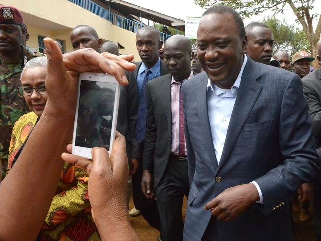 Kenya's President Uhuru Kenyatta speaks to the media after voting at a polling station. Picture: AFP