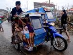 Children pack a motorbike's sidecar as they travel along a street in an area devastated by Typhoon Haiyan on in Leyte, Philippines. Picture: Getty Images