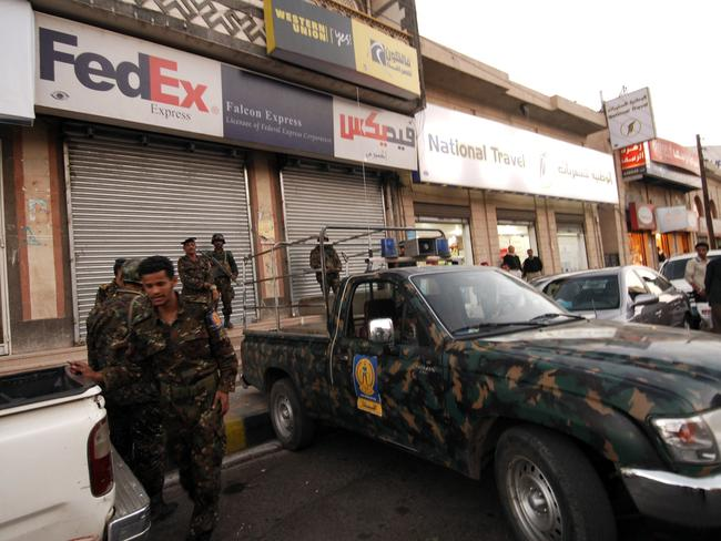 Yemeni security are seen in this file photo outside a branch of FedEx in Sanaa after explosives were found in air parcels sent to US synagogues in 2010. Picture: AFP/Mohammad Huwais.