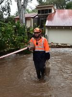SES Metro South volunteer George Boxhall carries sandbags at a flooded home on Fife Avenue, Torrens Park. Picture: Campbell Brodie