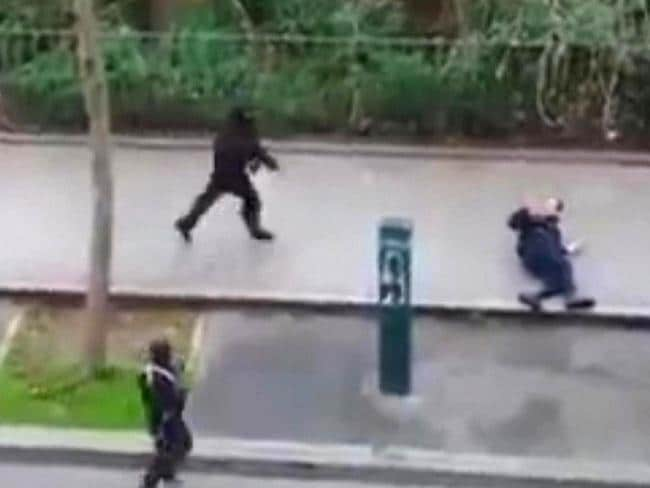 Masked gunman run towards a victim of their gun fire outside the French satirical newspaper Charlie Hebdo's office, in Paris. (AP Photo) NO SALES