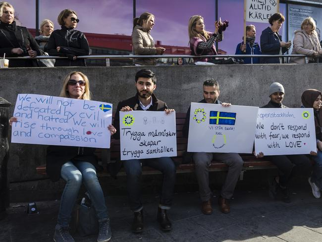People hold signs of solidarity on Sergels square after a peace demonstration on April 9, 2017 in Stockholm, Sweden. Picture: Getty.