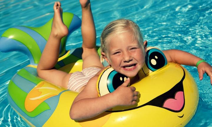 blond girl lying on her front in an inflatable boat in a swimming pool