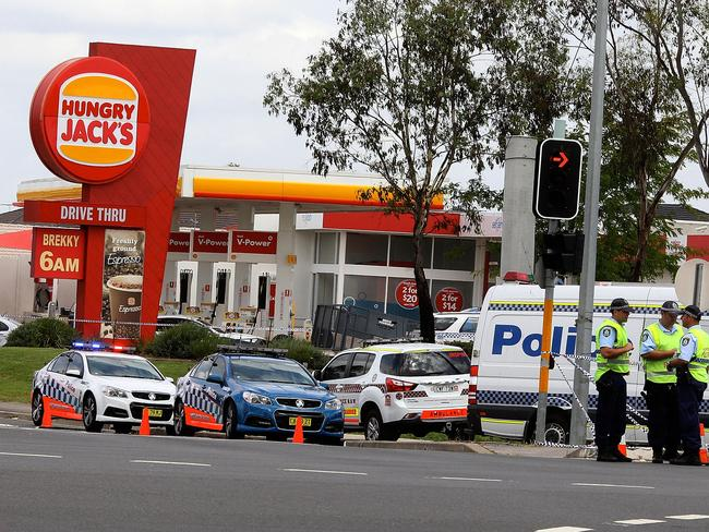 Police investigate the shooting, outside Hungry Jack's. Picture: Ben Rushton