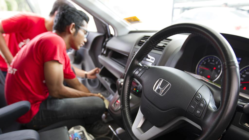 A Honda technician works on an airbag during a free airbag replacement event in Kuala Lumpur, Malaysia. A Malaysian man whose wife's death is one of at least 16 blamed on airbag defects has sued Japanese automaker Honda and the Takata in a US court, saying he wants the companies to disclose more about the dangers. Picture: Lim Huey Teng