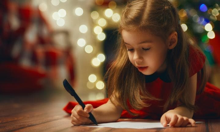 small child writes the letter to Santa