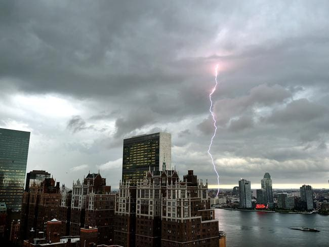Fierce winds and heavy rain forecast ... Lightning strikes in the sky over the East River, New York City.