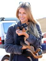 Jennifer Hawkins plays with a puppy that wandered on to the set. Picture: Alex Coppel