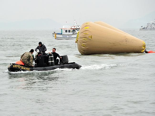 Slim chance of survival ... South Korean rescue teams search for the missing passengers near buoys installed to mark the position of the capsized ferry off Jindo. Picture: Jung Yeon-Je
