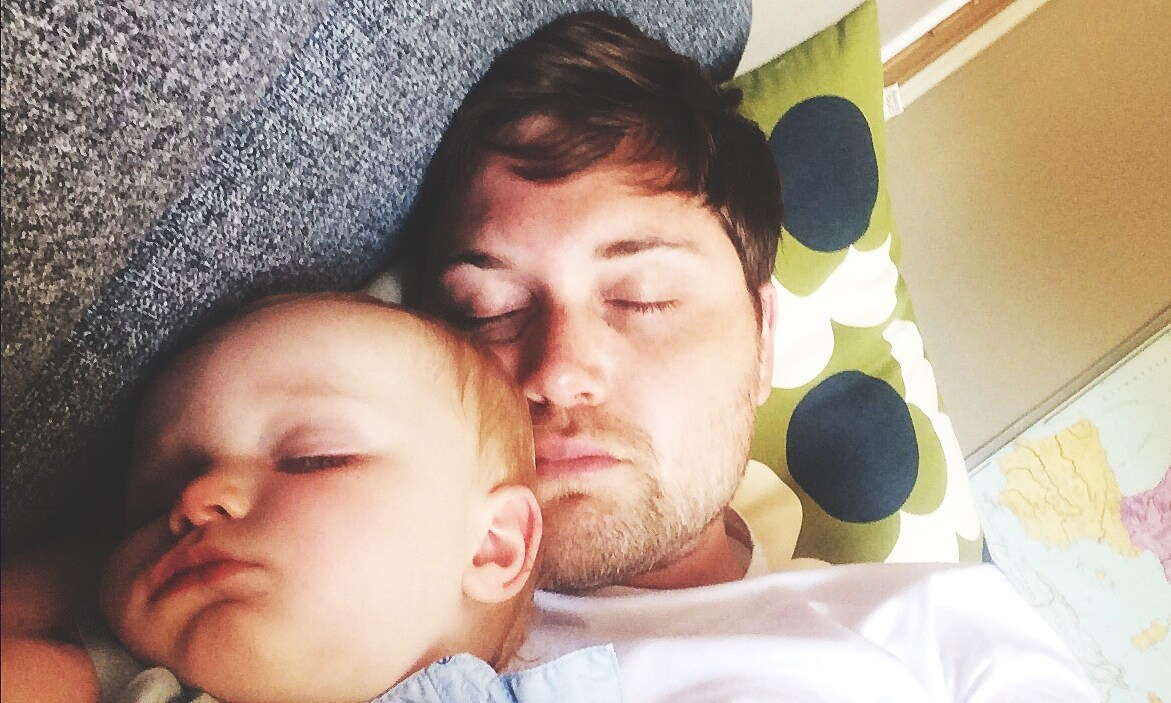 Close-Up Of Toddler Boy Sleeping Beside Father At Home