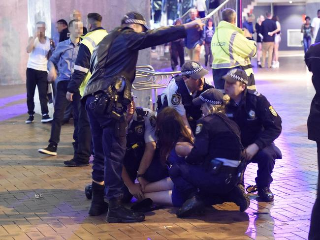 Police restrain night-clubbers during the brawl at Cockle Bay Wharf early yesterday. Picture: Gordon McComiskie