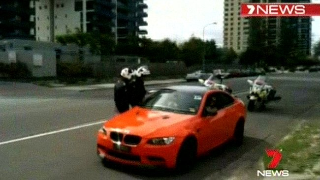Police officers speak to Bernard Tomic as he sits in his orange BMW. Image: Seven News