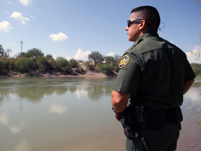 A real border patrol agent looks at Mexico across the Rio Grande in Texas.