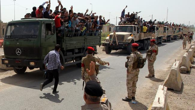 Iraqi men who volunteered to join the fight against a major offensive by jihadists in northern Iraq stand on army trucks as they leave a recruiting center in the capital Baghdad. Picture: AFP/Ali Al-Saadi