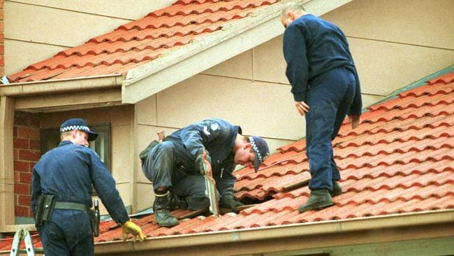 Police remove roof tiles during investigation of Debs' house in Springfield Drive, Narre Warren, in July, 2000.