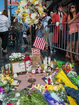Flowers are placed on Robin Williams' Walk of Fame star.