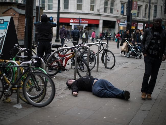 A man lies passed out on the pavement, as people walk by. Picture: Joel Goodman/LNP