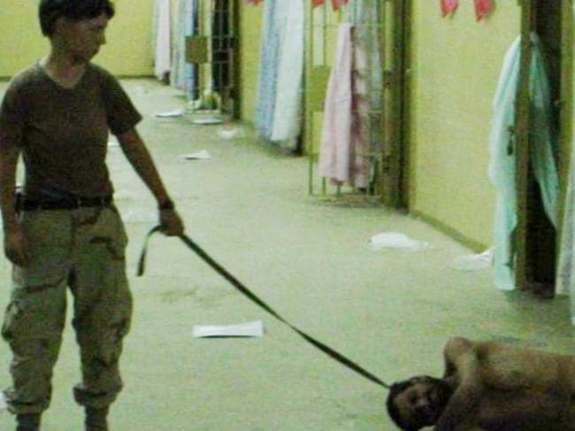 The infamous image from Abu Ghraib shows Private Lynndie England holding a leash attached to a detainee in 2003.