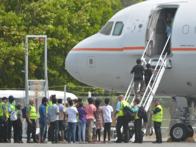 Asylum seekers prepare to board a plane at Cocos Island to fly to the Curtin Detention Centre in Western Australia. Picture: