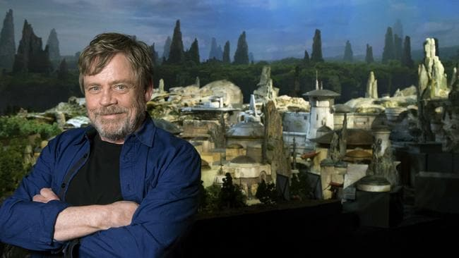 In this Friday, July 14, 2017 photo provided by Disney Parks, Mark Hamill, from the upcoming film 'Star Wars: The Last Jedi,' who was among the first to see a fully detailed model of Disney Parks' new Star Wars-themed land, poses while visiting D23 Expo in Anaheim, Calif. It was announced at the Disney fan event that the all-new 14-acre land will be called 'Star Wars: Galaxy's Edge' when it opens in 2019 at Disneyland Resort in California and Walt Disney World Resort in Florida. (Joshua Sudock/Disney Parks via AP)