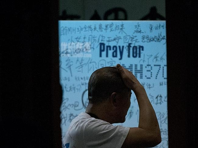 "Search for answeres...One of the relatives of Chinese passengers on board Malaysia Airlines Flight 370 reacts during a briefing by Malaysian officials at a Beijing hotel. A message behind him reads: ""Dear husband, you must stay strong, I am waiting for you. My dear, please be back soon."" Picture: AP"