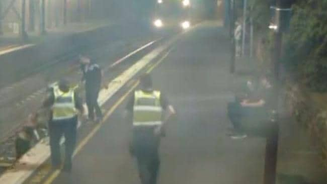 PSOs rush to the aid of a woman on the tracks. Picture: Victoria Police