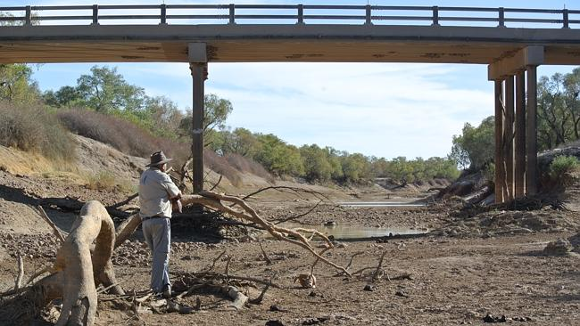 Long time Birdsville resident Don Rowlands stands near the base of the bridge of the bone-dry Diamantina River.