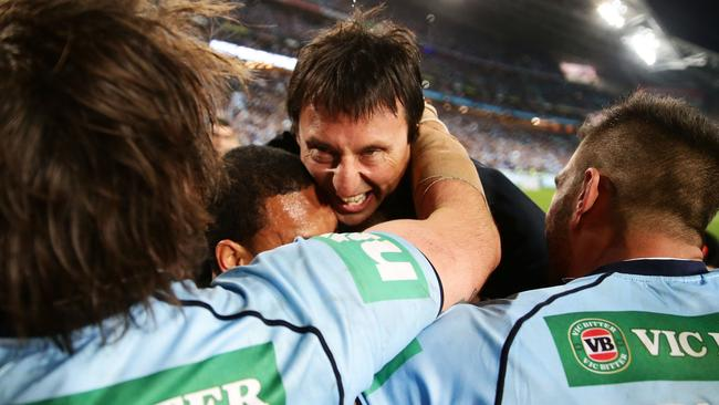 Head coach Laurie Daley is swallowed up by his Blues players.