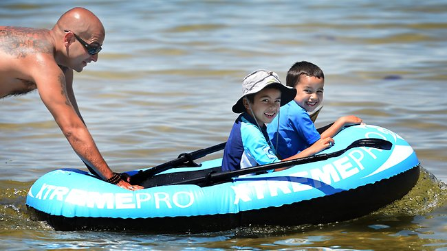 Cris Prado pushes Krishna Mertono, 7, and his brother Jai, 5, in their inflatable boat. Picture: Tony Gough