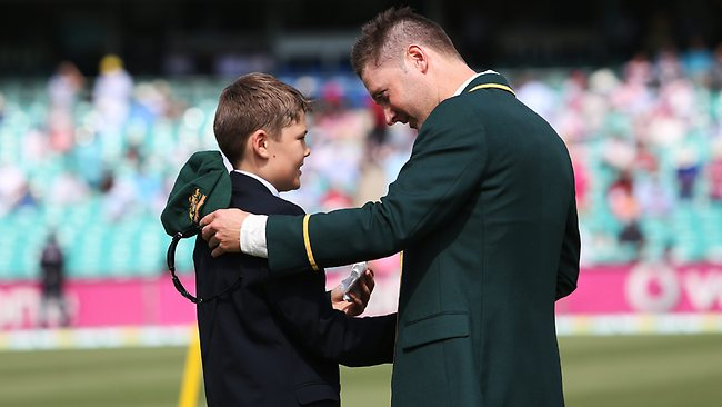 Tony Greig's son, Tom, hands Australian captain Michael Clarke his father's neckchief to wear in the Third Test at the SCG. Picture: Phil Hillyard