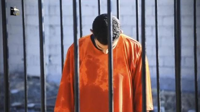 Jordanian pilot Muath al-Kasasbeh is seen standing in a cage before Islamic State militants set him alight then release a video of his murder. Picture: Reuters.