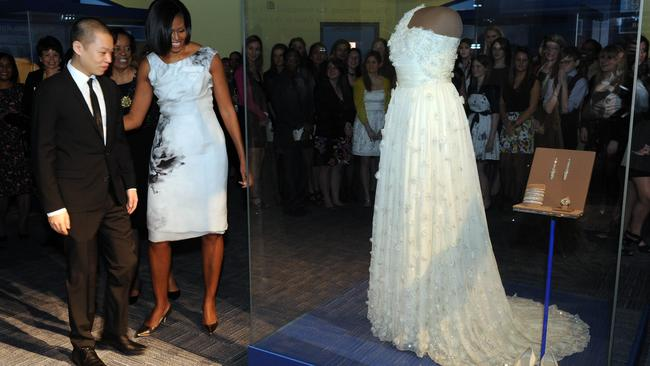 US First Lady Michelle Obama and designer Jason Wu look at a display of her inaugural gown, jewelleries and shoes at the Smithsonian's National Museum of American History in Washington on March 9, 2010. Picture: Jewel Samad/AFP
