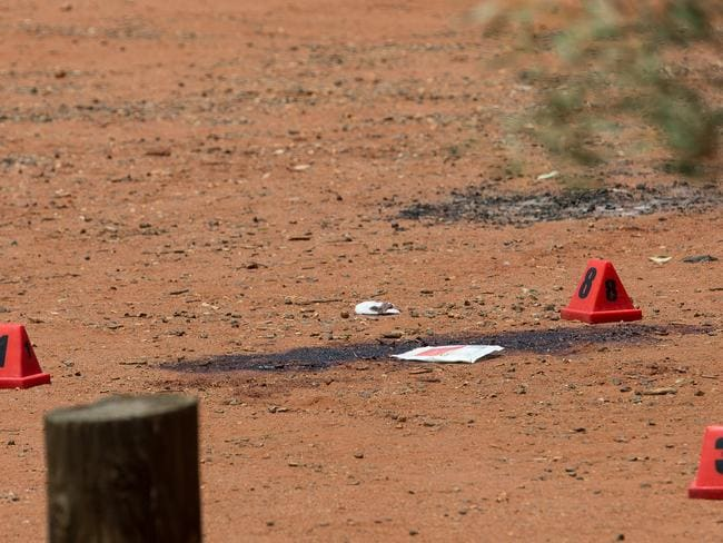 Police evidence markers near a big blood stain in the dirt.