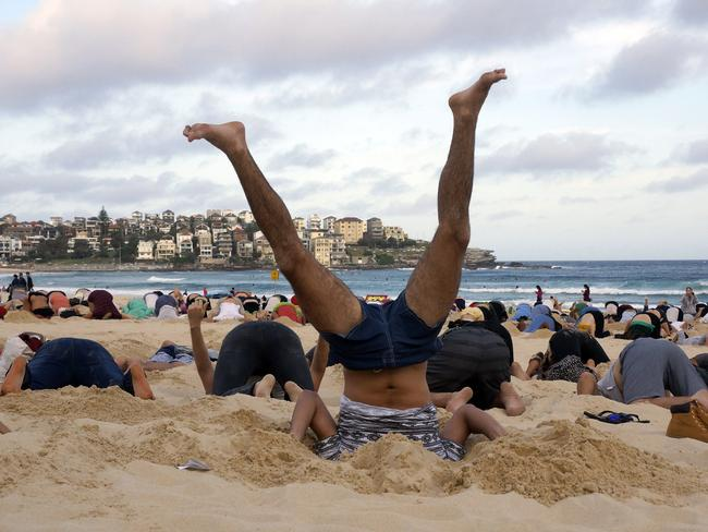 Climate change ... Protesters bury their heads in the sands of Bondi Beach to send a message to Mr Abbott about the dangers of climate change. Picture: AFP PHOTO / 350.ORG / TIM COLE