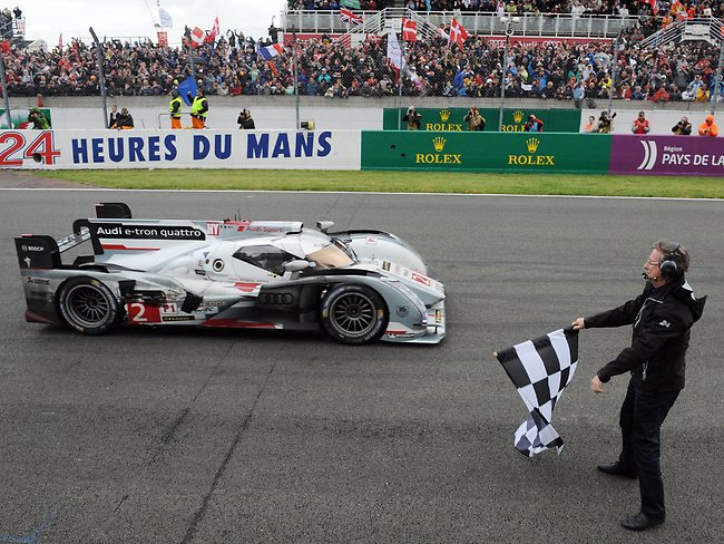 Danish driver Tom Kristensen in his Audi R18 E-Tron Quattro N2 takes the chequered flag at the end of the 90th edition Le Mans 24 hours endurance race.