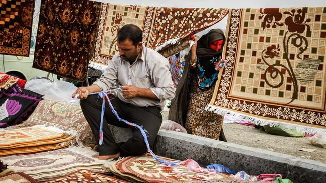 A carpet seller at the weekly 'Panjshambe Bazaar', Minab, Iran. Photo: Brook Mitchell
