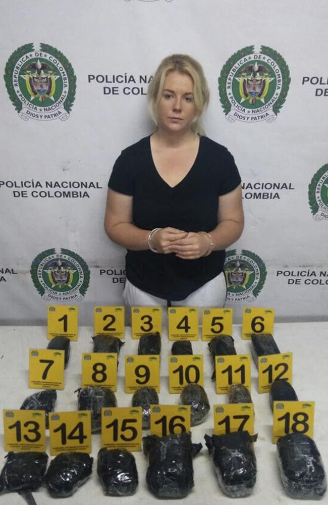South Australian drug mule Cassandra Sainsbury handcuffed and posing with the cocaine packages from her suitcase. Picture: Colombian National Police